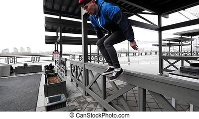Acrobat teenager jumping in sports grounds - performing a...