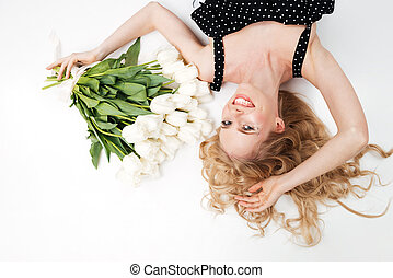 Top view of smiling woman lying on floor with flowers
