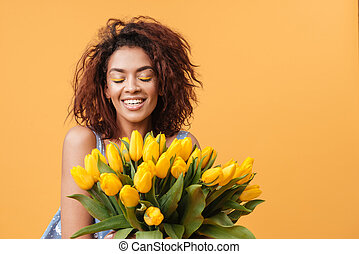 Smiling African woman with closed eyes holding bouquet of...