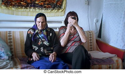 two women sitting in the room on the couch