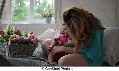Laughing baby girl and mother relaxing in bedroom - Portrait...