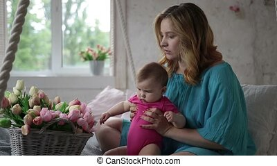 Adorable baby girl playing with tulip flowers - Side view of...