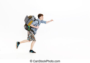 Young tourist with backpack running on white background....