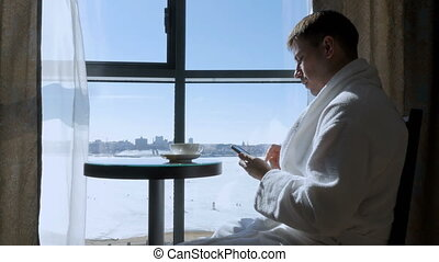 A young, attractive man sitting at a table by the window drinking tea, coffee and writing an SMS message on a mobile phone. Businessman. Sunny morning.