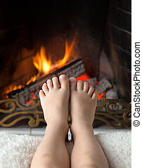 Childrens feet are heated in the fireplace - Childrens bare...