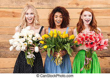 Three surprised women holding bouquets of flowers - Three...