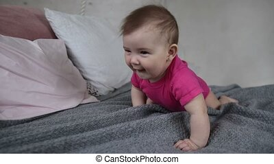 Joyful newborn child crawling on bed - Portrait of adorable...
