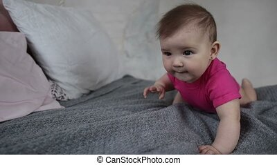 Laughing newborn child playing on bed - Adorable baby girl...