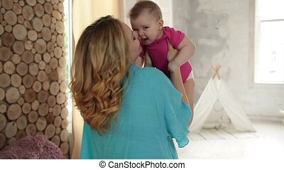 Caring mom kissing her adorable baby girl. - Young beautiful...