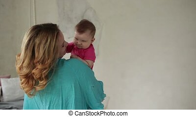 Loving mom kissing cute baby girl's nose - Affectionate...