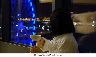 A young, beautiful woman in a white robe is drinking tea by the window. From the window a view of the Ferris wheel. Bokeh. Night