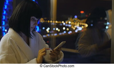 A young, beautiful woman in a white robe sits by the window, looks into the phone and writes an SMS message. From the window a view of the Ferris wheel. Hotel. Night