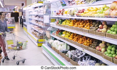 Young woman chooses fruits in the supermarket
