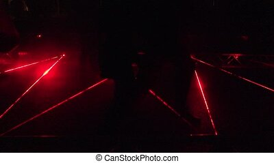 People climb over red protective laser beams outdoor at...