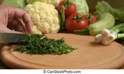 Cooking. Cutting fresh dill. Cutting fresh vegetables....