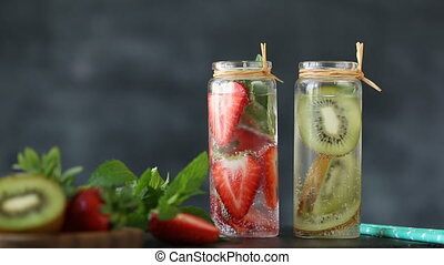 Homemade fruit water with kiwi and strawberry in jar,...
