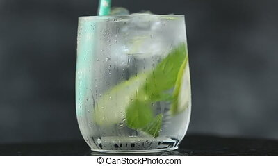 Mineral water in the glass with ice cubes,mint, lime and...