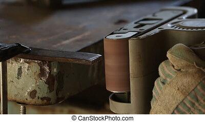 Metal worker grinding steel pipe, adult man using grinder to...