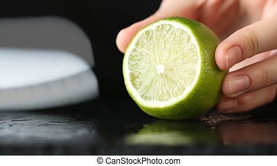 Close-up of woman hand cutting lime on black stone