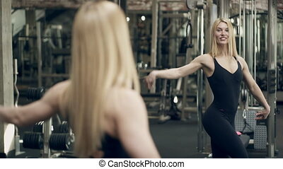 Bodybuilder woman stands in front of mirror inside gym....