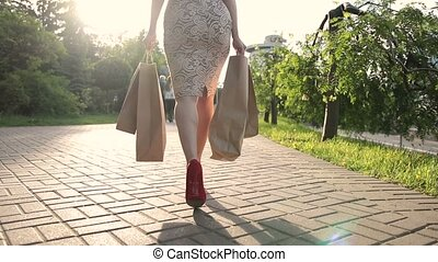 Shopper woman legs with shopping bags in street - Back view...