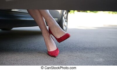 Woman in red high heels sitting in parked car - Low section...