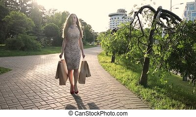 Elegant woman with shopping bags walking on street