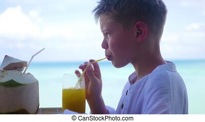 a young man in a cafe drinking a cocktail on terrace. outdoors. Coconut water