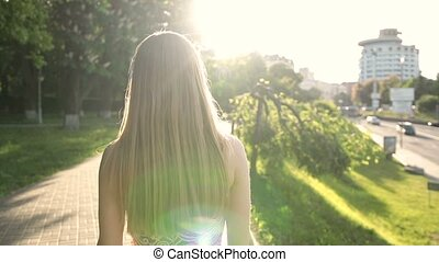 Charming blond woman walking on sidewalk at sunset - Back...