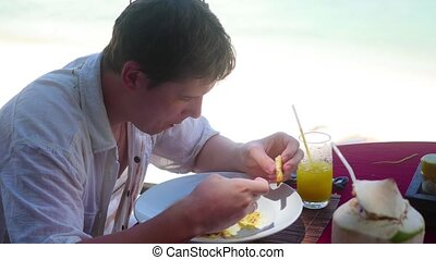 a young guy is eating out on the terrace. outdoors. Italian...