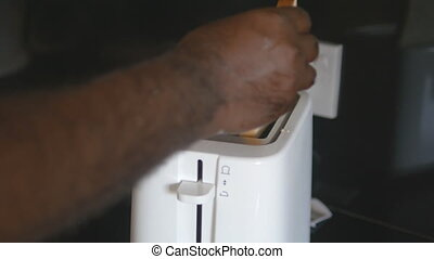 Male indian hands put in toaster two slices of bread, and...