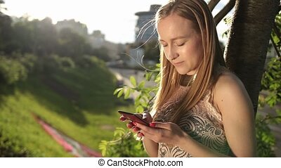 Joyful woman texting on smartphone in park - Pretty blonde...