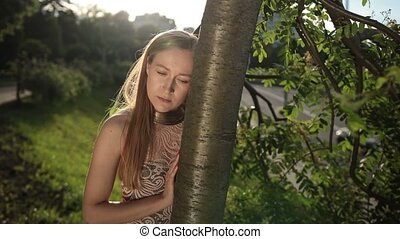 Portrait of pensive woman with head glued to tree. - Sad...