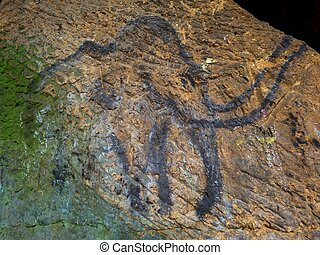Prehistoric art of mammoth in sandstone cave. Spotlight...