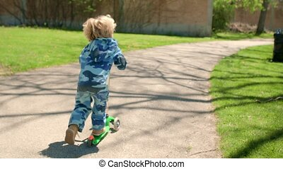 The boy is riding a scooter in the park