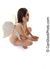 Fallen Angel - Attractive woman wearing angel wings sitting