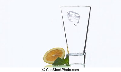 Ice Cubes Falling into the Glass. Slow Motion.