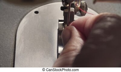 Threading the sewing machine. - Extreme close up of the hand...