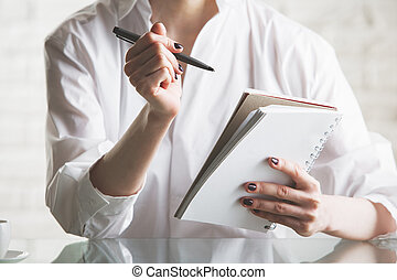 Girl writing in notepad - Close up and front view of girl's...
