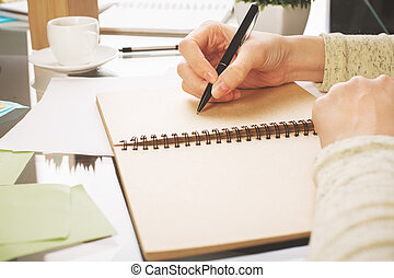 Woman writing in notepad side - Side view of woman's hands...