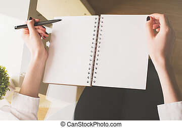 Woman writing in notepad - Top view of woman's hands writing...