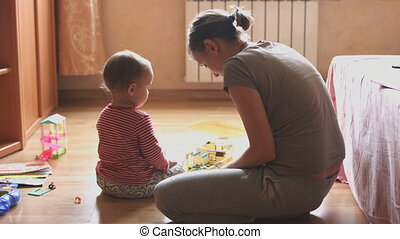 Mother and child playing in the room sitting on the floor....