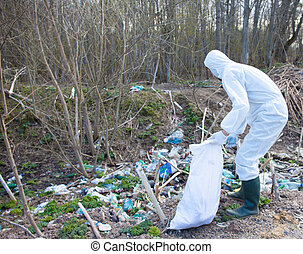 Volunteer man in white protective clothing collects garbage...