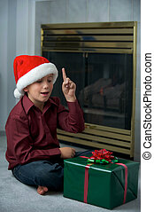Christmas boy and present - A young boy thinks he know what...