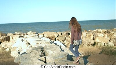The girl is walking along the rocks near the sea.