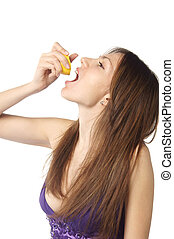 woman pouring juice from lemon slice in her mouth - profile...