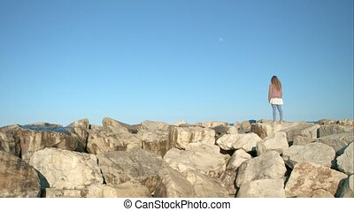 The girl looks at the moon standing on the rocks - Blonde...