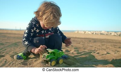 The boy is playing with a toy green dump truck on the beach.