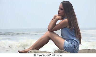 Teen Girl Sitting By Ocean