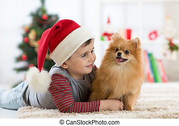 Happy kid little boy and dog at Christmas